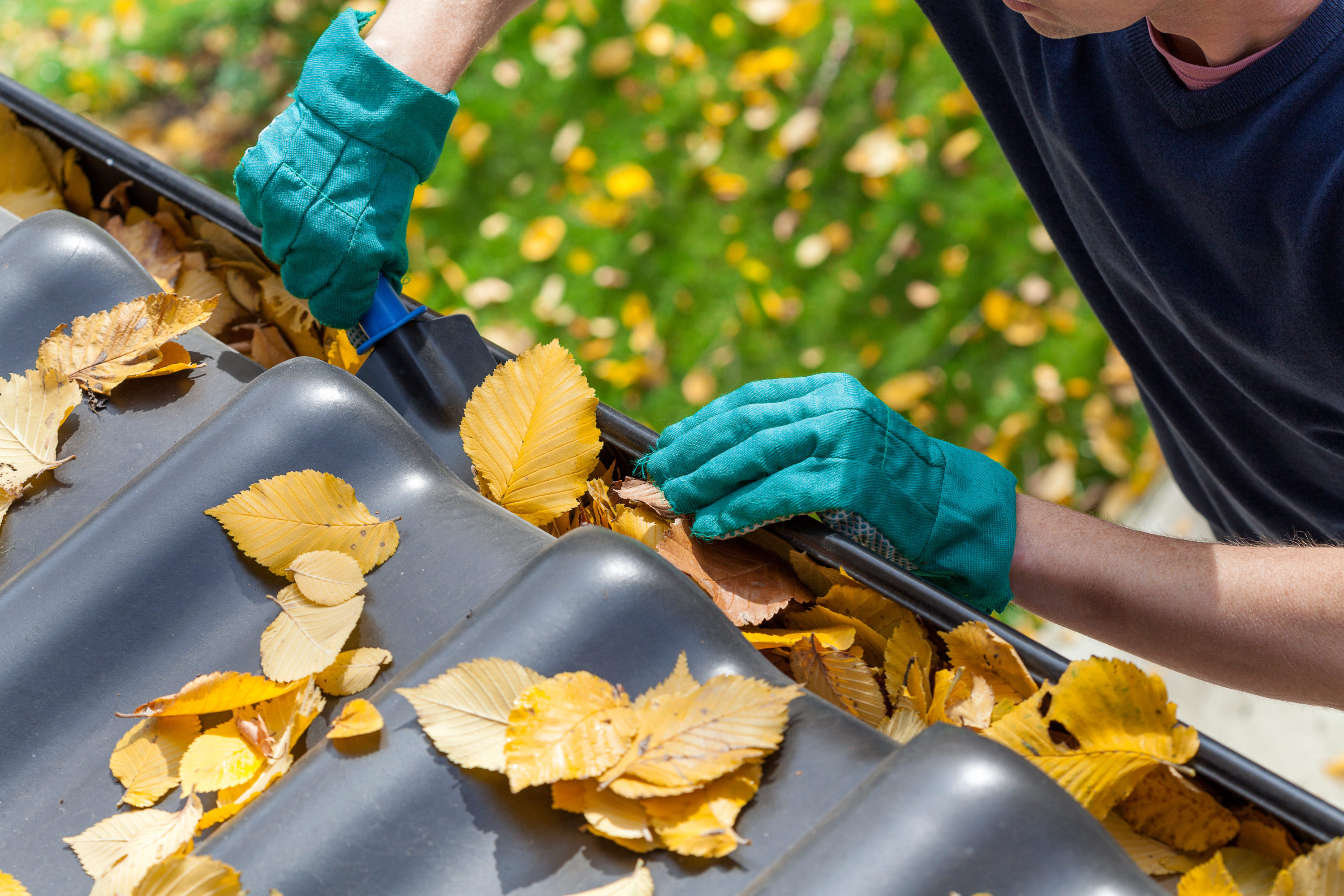 An ounce of prevention includes cleaning your home's gutters and downspouts. Man cleaning the gutter at a Penticton home.